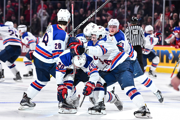MONTREAL, QC - JANUARY 04:   Members of Team United States jump on top of teammate Troy Terry #20 after he scored the game winning goal in a shootout during the 2017 IIHF World Junior Championship semifinal game against Team Russia at the Bell Centre on January 4, 2017 in Montreal, Quebec, Canada.  The Team United States defeated Team Russia 4-3 in a shootout.  (Photo by Minas Panagiotakis/Getty Images)